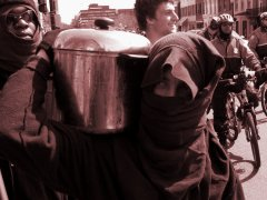 A person carries a pot of chili in a black bloc feeder march