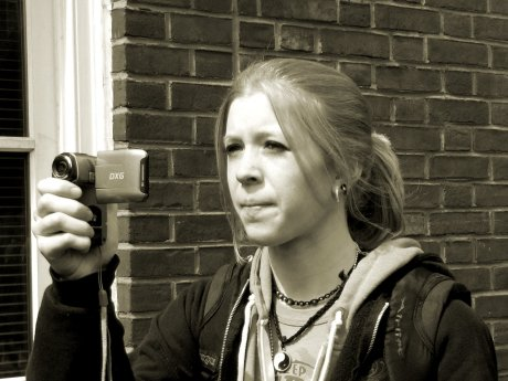 A woman films the event with a handheld camera