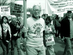 """Activist David Barrows holds up a sign while wearing a """"RESIST!"""" shirt"""