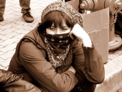 A masked demonstrator sits on the curb at the end of the march in Crystal City