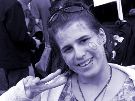 A woman gives a peace sign for the camera during a pause in the march