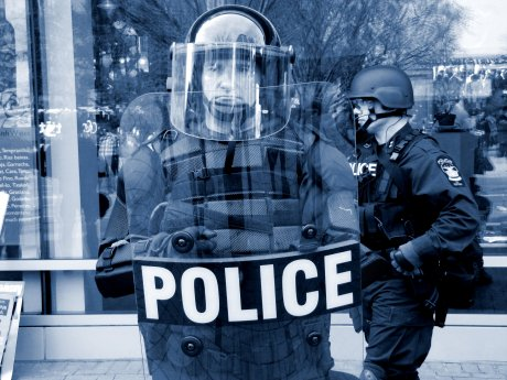 A police officer in full riot gear stands along the perimeter of the demonstration
