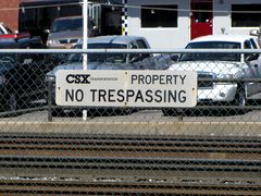 """""""NO TRESPASSING"""" sign on a fence at the edge of the CSX right of way."""