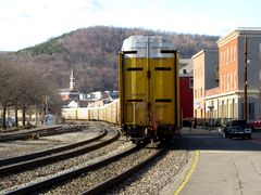 Final car of a freight train traveling through Cumberland. Town Clock Church is visible in the distance.