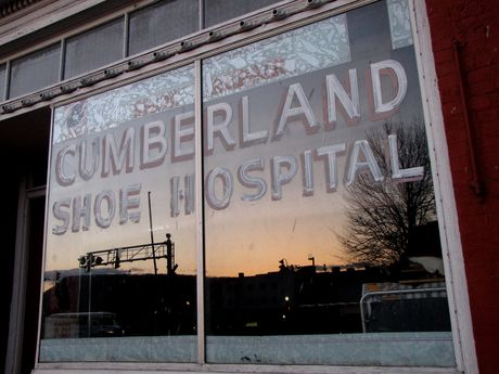 Window of Cumberland Shoe Hospital at sunset, reflecting the image of the town.
