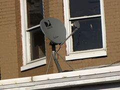 Satellite dish on the roof of a house's front porch.