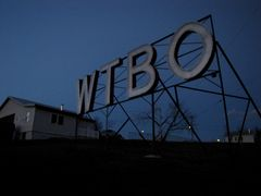 Darkened WTBO sign at night. The lighting pattern lights each letter sequentially, left to right, and then momentarily goes dark before repeating.