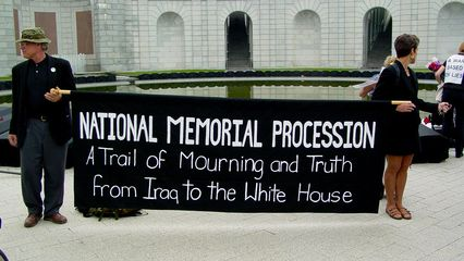 """The banner held by two participants says it all. """"A Trail of Mourning and Truth from Iraq to the White House"""". As evidenced by the participants' attire, and the sign, the predominant color was black, to symbolize mourning. As such, participants were strongly encouraged to wear black to this event."""