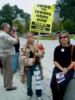 A few participants wore desert-style military fatigues. This woman wears a jacket while holding a sign for ANSWER Coalition.
