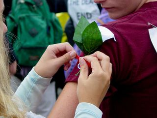 Some participants wore white flowers, illustrated here as one person attaches a white flower to the arm of another, using a red ribbon.
