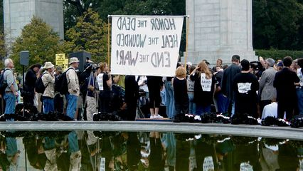 """From across the reflecting pool, the crowd is significant. Note the original wording on the banner of """"Honor the dead"""". This was changed on the other side of the sign to """"Mourn the dead"""". Presumably the former was to be the original term used, and was later changed after the banner was made. Considering that this is a funeral-style procession, """"Mourn"""" makes more sense."""