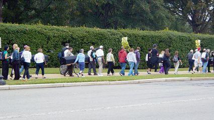 Marchers begin the walk to the White House along the sidewalk, headed into Washington.
