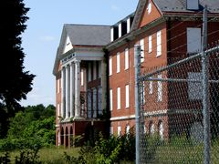 The east side of the Peery Building, beyond fencing around the main entrance to the original building