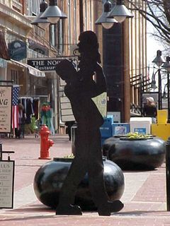 Throughout downtown, there's a number of black-painted wooden people in various poses. This one involves a man holding up a bust of what appears to be a man. Other ones involve a mother being pulled along by her kid, a woman carrying shopping bags, a man walking, and others.