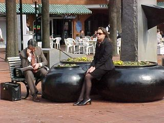 Beside the fountain, businesspeople wait, or conduct business by phone.