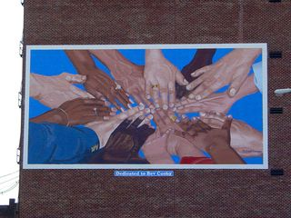 A mural is painted onto the bricks as a tribute to the Rev. Bev Cosby, a local minister, showing a laying of hands of people associated with Cosby. This mural, according to information I've found, is the first of a series that Lynchburg has planned for downtown.