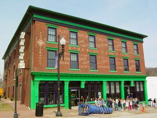 """One of the more interesting buildings near the river in Lynchburg is the J.W. Wood Building, home of the children's museum Amazement Square. The building has a cast-iron façade (painted green), and also historic painted signage reflecting the building's former use as a wholesale grocery firm and warehouse. One side of the building even shows the phrase """"Death to all insects"""", from the same era, referring to the insecticides once sold in the facility."""