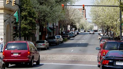 The streets in downtown Lynchburg, particularly Main Street, shown here, are mostly one-way, and feature brick crosswalks and intersections. Additionally, the streets are lined with trees, providing shade for the sidewalks.