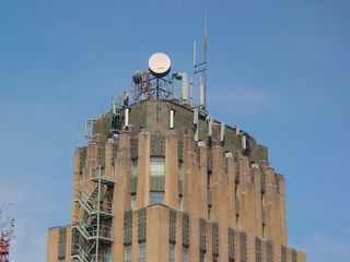 The roof of the building is home to various antennae and satellite dishes. A man can be seen standing on the roof.