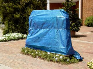 The sign for the Charles C. Yancey Municipal Building is hidden by shrubbery, while a fake church sign, shown here covered by a blue tarp, stands out in front.