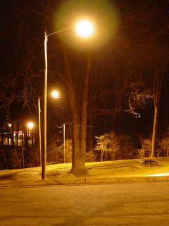 """Meanwhile, the parking lot's security lighting, illuminating everything around it, and providing contrast to the darkened sports facilities nearby, gives a glow as if to say, """"No matter what else happens in the world, it's going to be all right."""""""