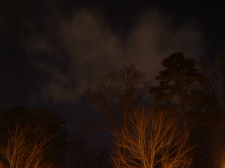 The orange-yellow glow of the security lighting also illuminates low lying clouds, with them reflecting the light back onto the ground.