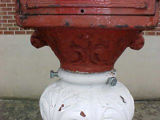Down below, bolts connect the box to the decorative pedestal.