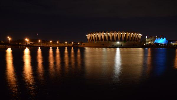 Hampton Coliseum, viewed from across Coliseum Lake, lit up at night.