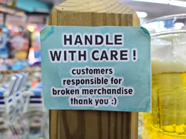 Sign at ILoveVA, a gift shop in Virginia Beach, Virginia, warning customers to handle the products with care, because they are responsible for broken merchandise.