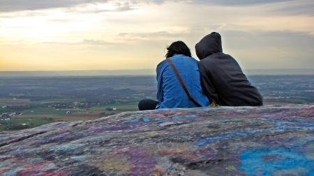 Two people sit on High Rock, looking down at a mobile device.
