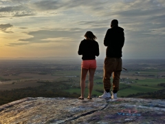 A man and a woman stand on High Rock, both interacting with their mobile devices.