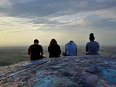 Four teens sit on High Rock, all interacting with their mobile devices.