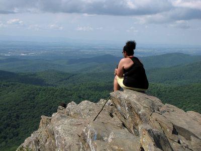 A woman sits at the summit of Humpback Rock