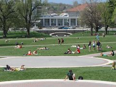 Students relax on the Quad. The new Forbes Performing Arts Center is under construction in the distance.