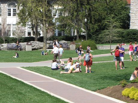 Students relax and converse on the Quad. Alumnae Hall is visible in the distance.