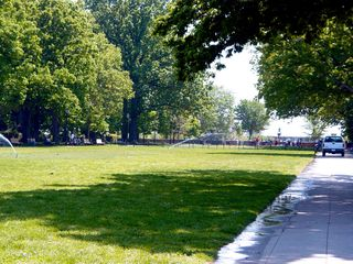 The upper level of Malcolm X Park is a wide grassy mall, shaded by trees around the edges.