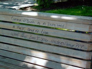 Four months after Inauguration Day, two benches still wore graffiti from the rally held in the park. One carries a penned message about George W. Bush, and the other carries a spray-painted anarchist symbol.