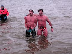 Two men in speedos pose in the water. Going by the expression on his face, the man on the left is very cold!
