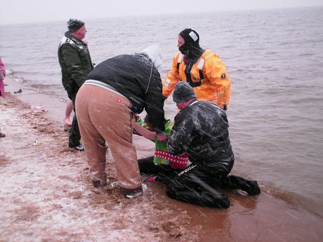 Event support staff help a woman who required rescue after she was unable to get out of the water on her own due to the cold.