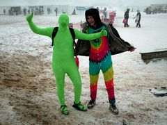 """A man in a """"green man"""" zentai suit and a man in a rainbow jumpsuit pose for the camera, all smiles. They were unable to plunge due to the cancellation of the 3:00 plunge."""