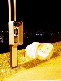 By day, it's an ordinary payphone. By night, an island of communication in a sea of light and dark.