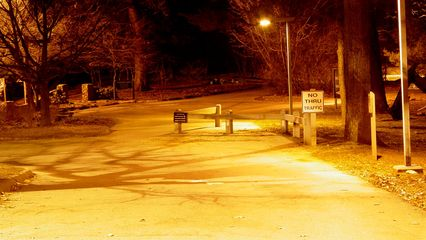 The road to the Mill Mountain Zoo glows in a bright orange color, with the Wildflower Garden shrouded in darkness.