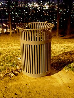 The trash receptacles, with the city beyond, normally a green color, appear brown by night...