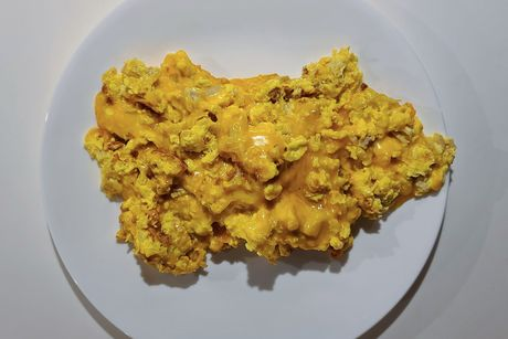 A plate of scrambled eggs with cheese.