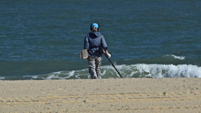 A person walks the beach while using a metal detector.