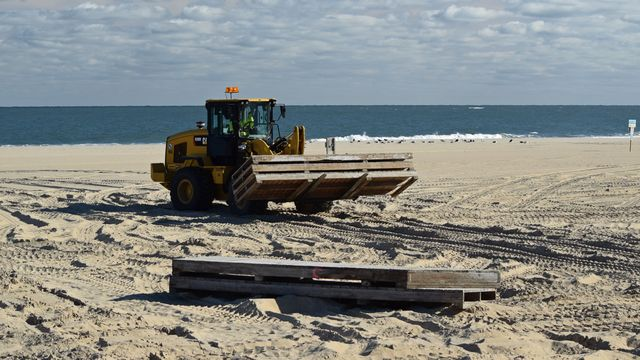 A large forklift moves pallets around on the beach.