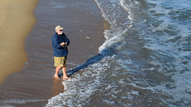 A man fishes in the ocean.