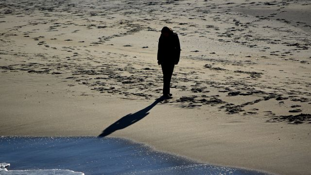 A woman walks along the beach.