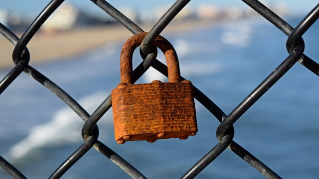 Rusted padlock attached to the chain link fencing on the Ocean City Fishing Pier.