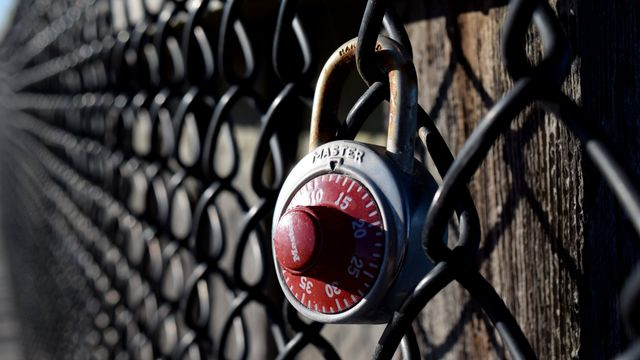 Combination lock attached to the chain link fencing on the Ocean City Fishing Pier.